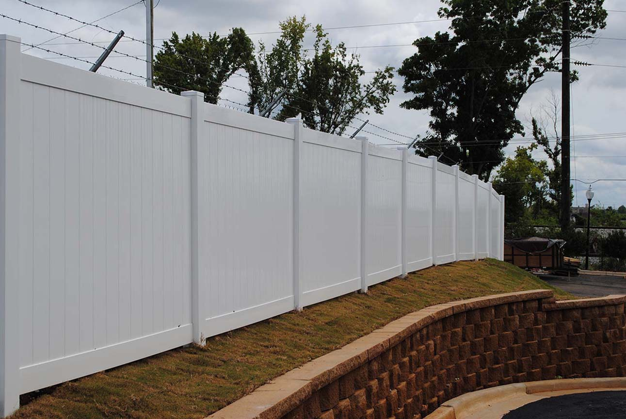 Vinyl Fence with Barbed Wires on top Hill. Vinyl Fence Anniston AL   The Fence Place
